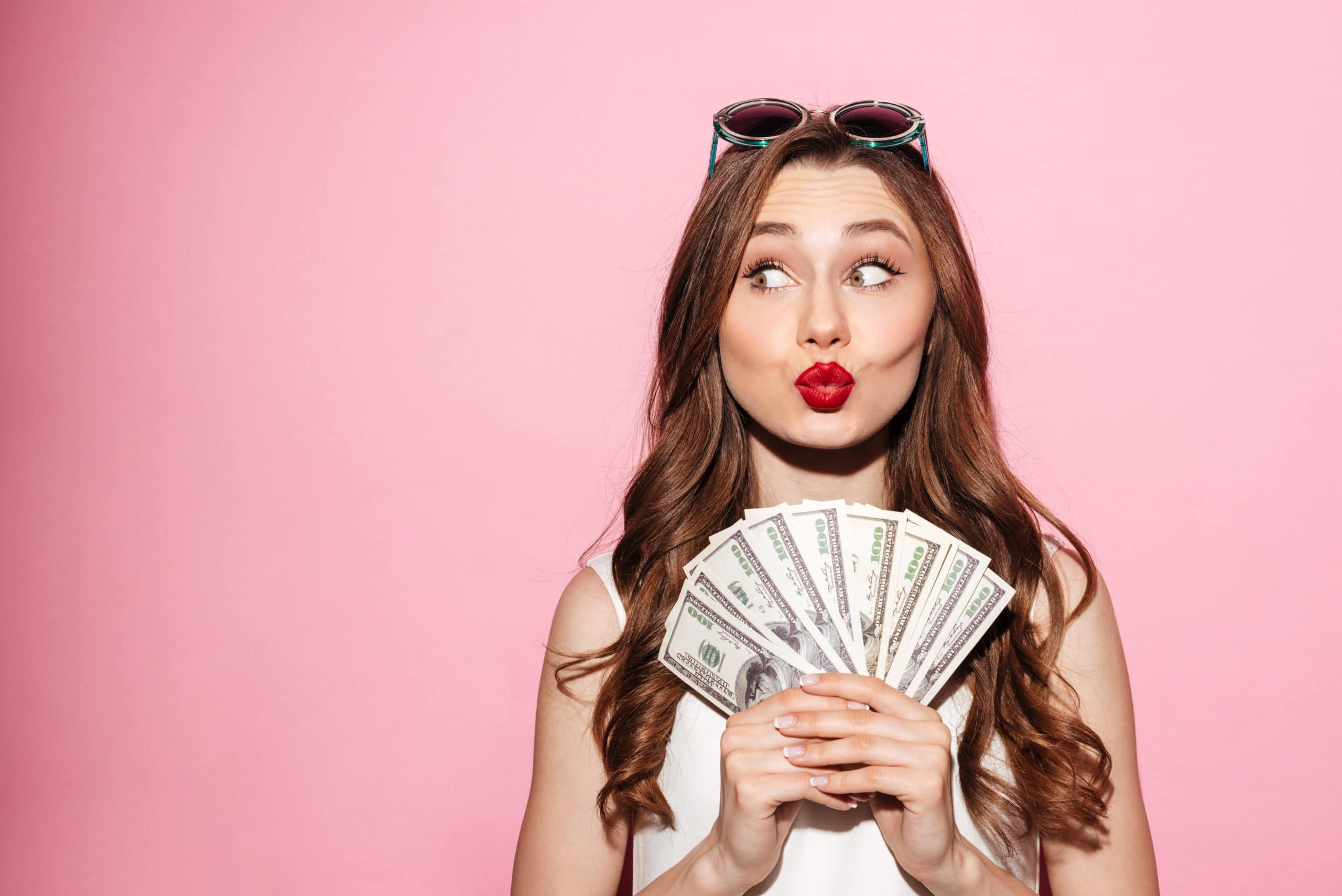 Picture of a funny young brunette lady in white summer dress holding money and looking aside over pink background.